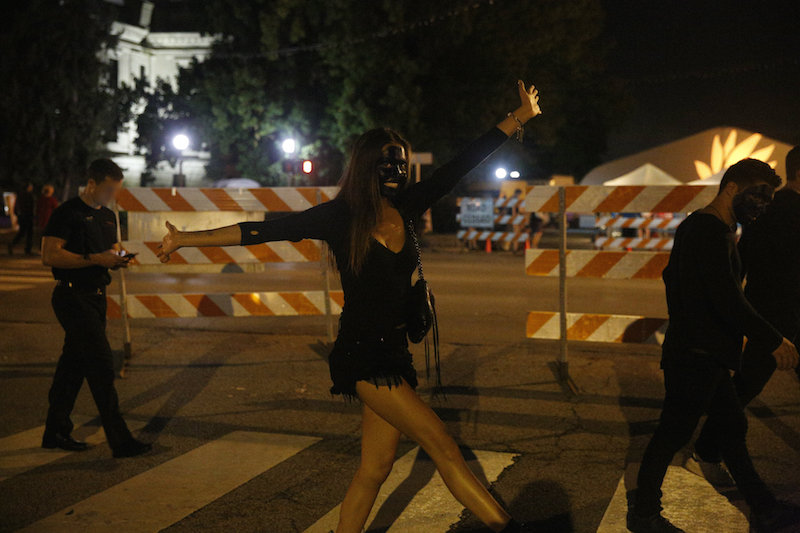 A white woman, probably an IU undergraduate student, not at all shy about the fact that her face is covered in dark paint. One of her friends (at right) has the same paint on his face. Saturday, September 17, 2016, downtown Bloomington, Indiana.